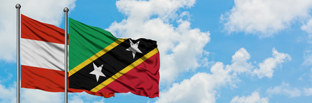 Austria and Saint Kitts And Nevis flag waving in the wind against white cloudy blue sky together. Diplomacy concept, international relations.