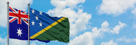 Australia and Solomon Islands flag waving in the wind against white cloudy blue sky together. Diplomacy concept, international relations.