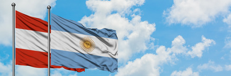 Austria and Argentina flag waving in the wind against white cloudy blue sky together. Diplomacy concept, international relations.