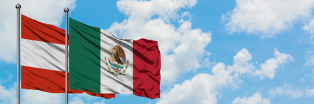 Austria and Mexico flag waving in the wind against white cloudy blue sky together. Diplomacy concept, international relations.