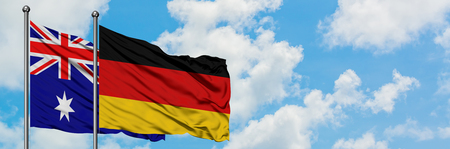 Australia and Germany flag waving in the wind against white cloudy blue sky together. Diplomacy concept, international relations.