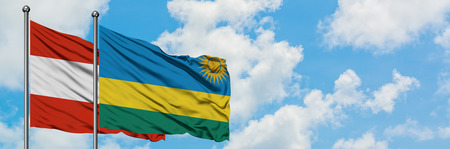 Austria and Rwanda flag waving in the wind against white cloudy blue sky together. Diplomacy concept, international relations. Banco de Imagens