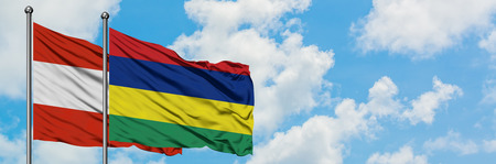 Austria and Mauritius flag waving in the wind against white cloudy blue sky together. Diplomacy concept, international relations. Banco de Imagens
