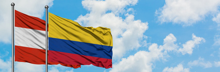 Austria and Colombia flag waving in the wind against white cloudy blue sky together. Diplomacy concept, international relations.
