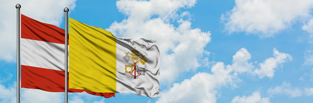Austria and Vatican City flag waving in the wind against white cloudy blue sky together. Diplomacy concept, international relations.