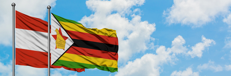 Austria and Zimbabwe flag waving in the wind against white cloudy blue sky together. Diplomacy concept, international relations. Imagens
