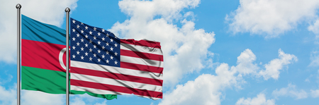 Azerbaijan and United States flag waving in the wind against white cloudy blue sky together. Diplomacy concept, international relations.