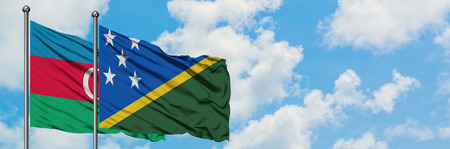 Azerbaijan and Solomon Islands flag waving in the wind against white cloudy blue sky together. Diplomacy concept, international relations.