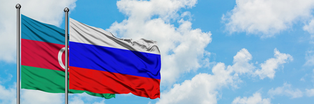 Azerbaijan and Russia flag waving in the wind against white cloudy blue sky together. Diplomacy concept, international relations.