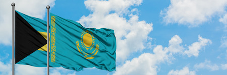 Bahamas and Kazakhstan flag waving in the wind against white cloudy blue sky together. Diplomacy concept, international relations. Stock Photo