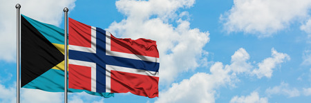 Bahamas and Norway flag waving in the wind against white cloudy blue sky together. Diplomacy concept, international relations.