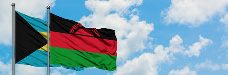 Bahamas and Malawi flag waving in the wind against white cloudy blue sky together. Diplomacy concept, international relations. Stock Photo
