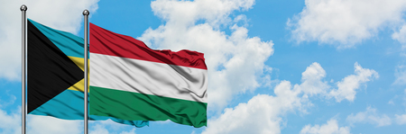 Bahamas and Hungary flag waving in the wind against white cloudy blue sky together. Diplomacy concept, international relations.