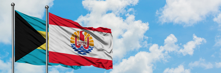 Bahamas and French Polynesia flag waving in the wind against white cloudy blue sky together. Diplomacy concept, international relations. Stock Photo - 123072271