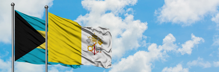 Bahamas and Vatican City flag waving in the wind against white cloudy blue sky together. Diplomacy concept, international relations.