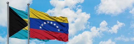 Bahamas and Venezuela flag waving in the wind against white cloudy blue sky together. Diplomacy concept, international relations. Stock Photo