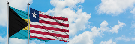 Bahamas and Liberia flag waving in the wind against white cloudy blue sky together. Diplomacy concept, international relations. Stock Photo - 123072277