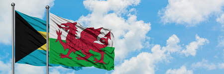 Bahamas and Wales flag waving in the wind against white cloudy blue sky together. Diplomacy concept, international relations. Stock Photo