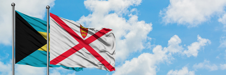 Bahamas and Jersey flag waving in the wind against white cloudy blue sky together. Diplomacy concept, international relations. Stock Photo - 123072300