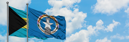 Bahamas and Northern Mariana Islands flag waving in the wind against white cloudy blue sky together. Diplomacy concept, international relations.