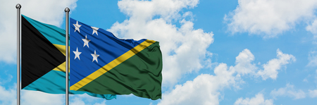 Bahamas and Solomon Islands flag waving in the wind against white cloudy blue sky together. Diplomacy concept, international relations.