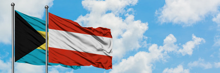 Bahamas and Austria flag waving in the wind against white cloudy blue sky together. Diplomacy concept, international relations.