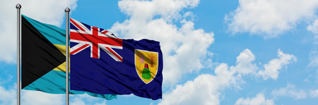 Bahamas and Turks And Caicos Islands flag waving in the wind against white cloudy blue sky together. Diplomacy concept, international relations. Stock Photo