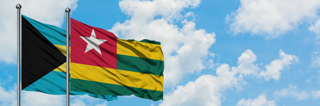 Bahamas and Togo flag waving in the wind against white cloudy blue sky together. Diplomacy concept, international relations. Фото со стока