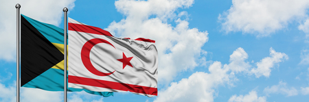 Bahamas and Northern Cyprus flag waving in the wind against white cloudy blue sky together. Diplomacy concept, international relations. Stock Photo