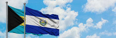 Bahamas and El Salvador flag waving in the wind against white cloudy blue sky together. Diplomacy concept, international relations.