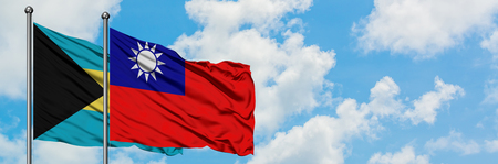 Bahamas and Taiwan flag waving in the wind against white cloudy blue sky together. Diplomacy concept, international relations. Фото со стока