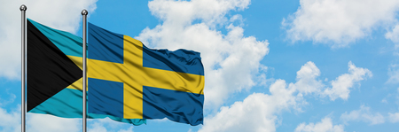 Bahamas and Sweden flag waving in the wind against white cloudy blue sky together. Diplomacy concept, international relations.