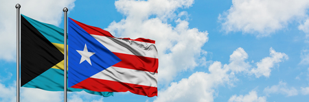 Bahamas and Puerto Rico flag waving in the wind against white cloudy blue sky together. Diplomacy concept, international relations. Stock Photo - 123073029