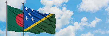 Bangladesh and Solomon Islands flag waving in the wind against white cloudy blue sky together. Diplomacy concept, international relations.