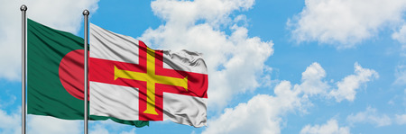Bangladesh and Guernsey flag waving in the wind against white cloudy blue sky together. Diplomacy concept, international relations.