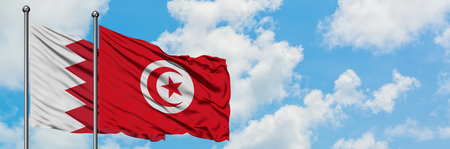 Bahrain and Tunisia flag waving in the wind against white cloudy blue sky together. Diplomacy concept, international relations.