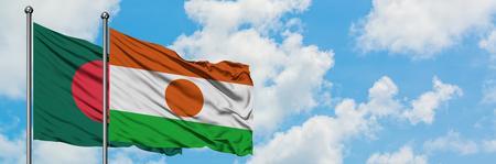 Bandera de Bangladesh y Níger ondeando en el viento contra el cielo azul nublado blanco juntos. Concepto de diplomacia, relaciones internacionales.