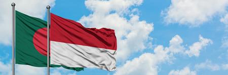 Bandera de Bangladesh y Mónaco ondeando en el viento contra el cielo azul nublado blanco juntos. Concepto de diplomacia, relaciones internacionales. Foto de archivo