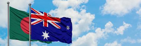 Bangladesh y la isla Heard y la bandera de las Islas Mcdonald ondeando en el viento contra el cielo azul nublado blanco juntos. Concepto de diplomacia, relaciones internacionales.