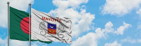 Bangladesh y Mayotte bandera ondeando en el viento contra el cielo azul nublado blanco juntos. Concepto de diplomacia, relaciones internacionales.