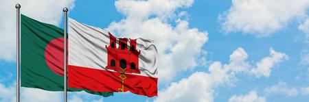 Bandera de Bangladesh y Gibraltar ondeando en el viento contra el cielo azul nublado blanco juntos. Concepto de diplomacia, relaciones internacionales.