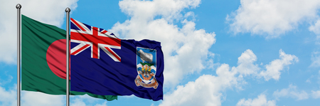 Bangladesh and Falkland Islands flag waving in the wind against white cloudy blue sky together. Diplomacy concept, international relations. Foto de archivo