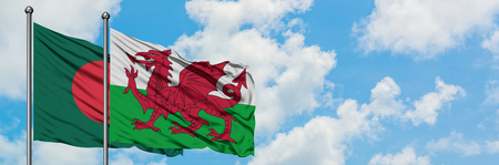 Bangladesh and Wales flag waving in the wind against white cloudy blue sky together. Diplomacy concept, international relations. Stock Photo
