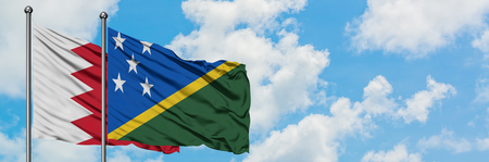 Bahrain and Solomon Islands flag waving in the wind against white cloudy blue sky together. Diplomacy concept, international relations.