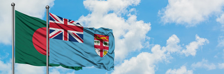 Bangladesh and Fiji flag waving in the wind against white cloudy blue sky together. Diplomacy concept, international relations.