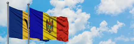 Barbados and Moldova flag waving in the wind against white cloudy blue sky together. Diplomacy concept, international relations.