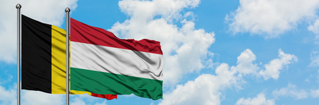 Belgium and Hungary flag waving in the wind against white cloudy blue sky together. Diplomacy concept, international relations.