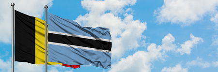 Belgium and Botswana flag waving in the wind against white cloudy blue sky together. Diplomacy concept, international relations. 免版税图像