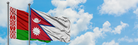 Belarus and Nepal flag waving in the wind against white cloudy blue sky together. Diplomacy concept, international relations. Фото со стока