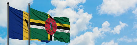Barbados and Dominica flag waving in the wind against white cloudy blue sky together. Diplomacy concept, international relations.
